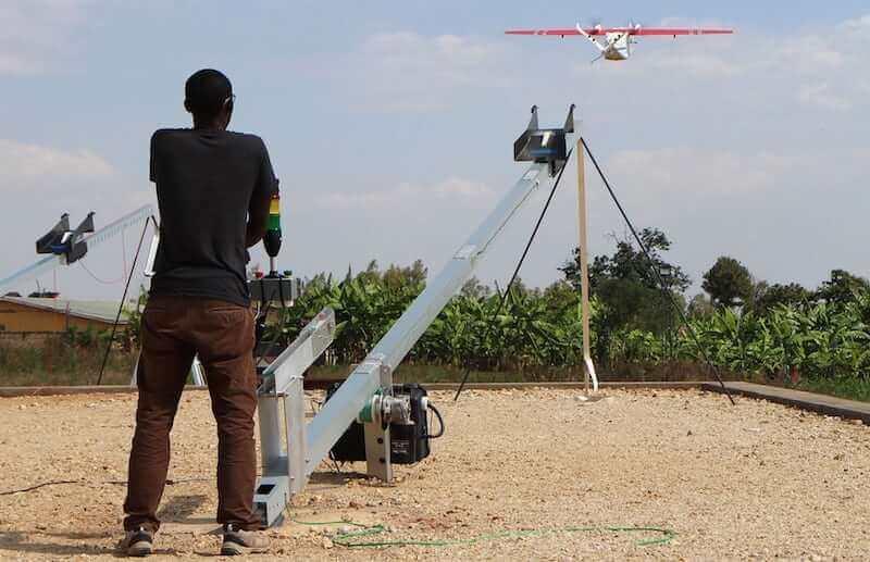 Technik pracownik Zipline uruchamia drone w Muhanga
