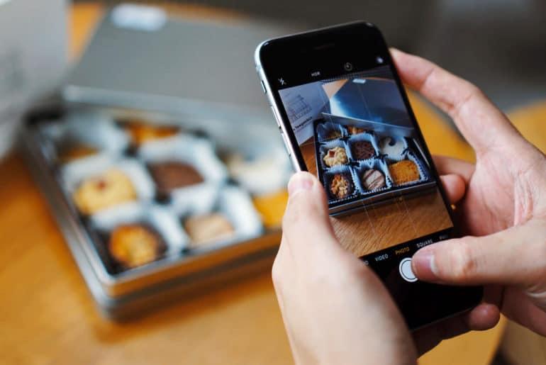 Dziewczyna robi zdjęcie słodyczom swoim telefonem