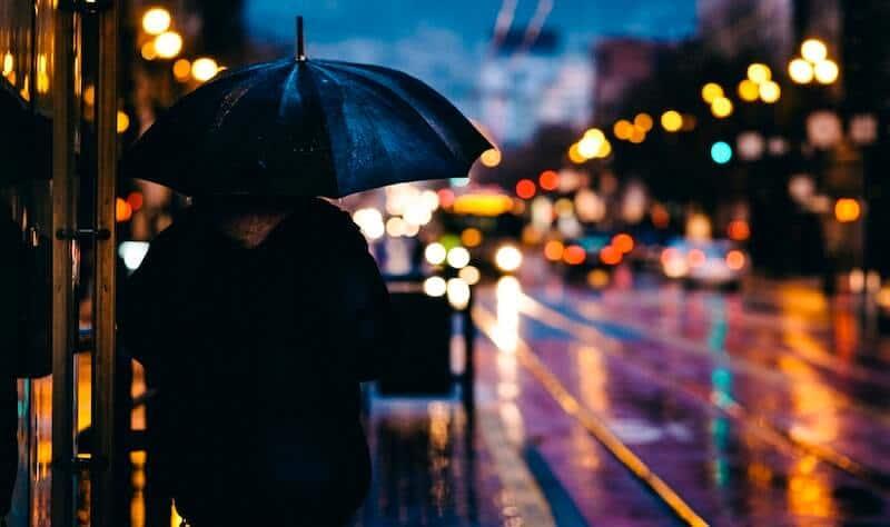 Na tym zdjęciu widać na pierwszym planie osobę z parasolem i ładnie rozmyte tło (światła pojazdów tworzą ładny efekt bokeh)