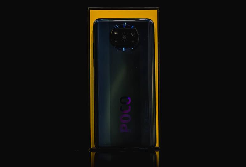Telefon Poco X3 NFC na tle swojego opakowania