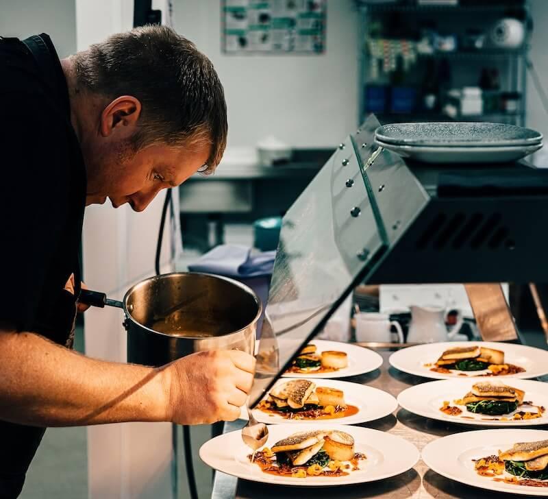 Kucharz przygotowuje jedzenie do serwowania